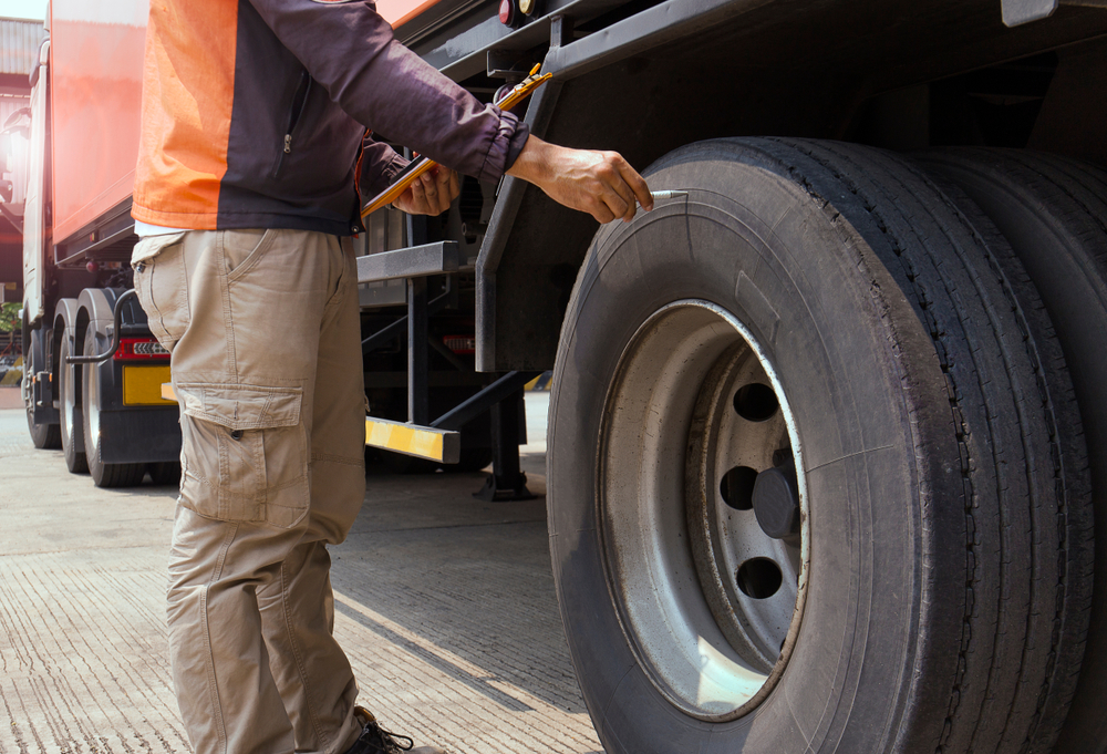 A man checking the tires of a truck.