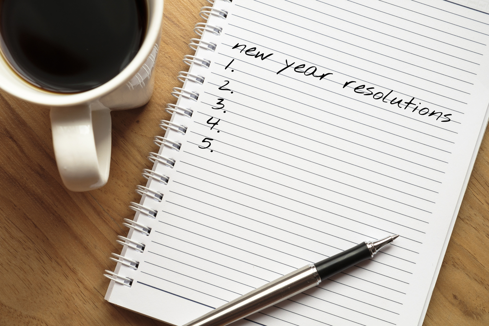 """A notepad with the words """"New Years Resolution"""" on it."""