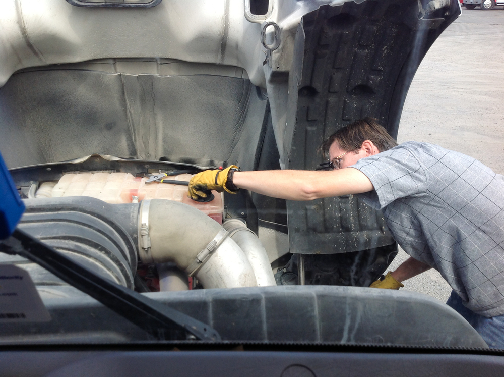 A man wearing gloves checking out the inside of a truck.