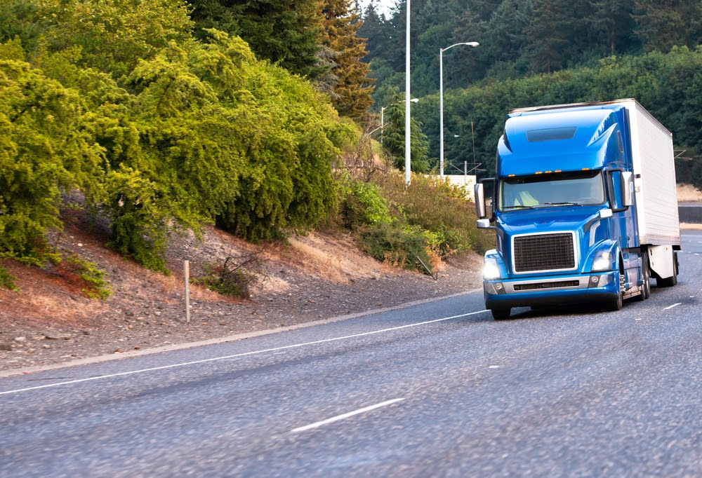 A blue semi truck on the road.